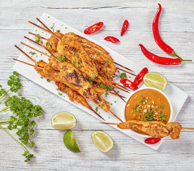 Chicken satay on skewers sprinkled with finely chopped parsley on a white rectangular plate with peanut sauce