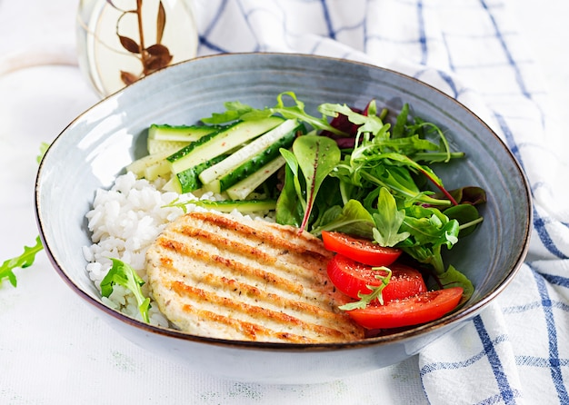 Chicken schnitzel or cutlet, poultry meat grilled and boiled white rice with fresh salad