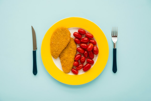 Chicken schnitzel and little tomato on yellow plate