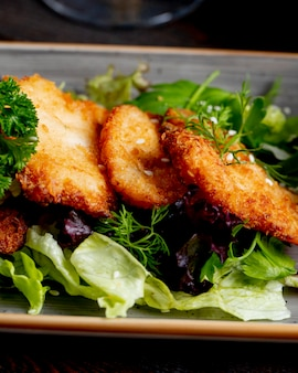 Chicken schnitzel served with lettuce and greens