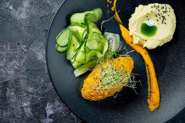 Куриный шницель с картофельным пюре, желтым соусом и огурцами. котлета по-киевски. закрыть вверх
