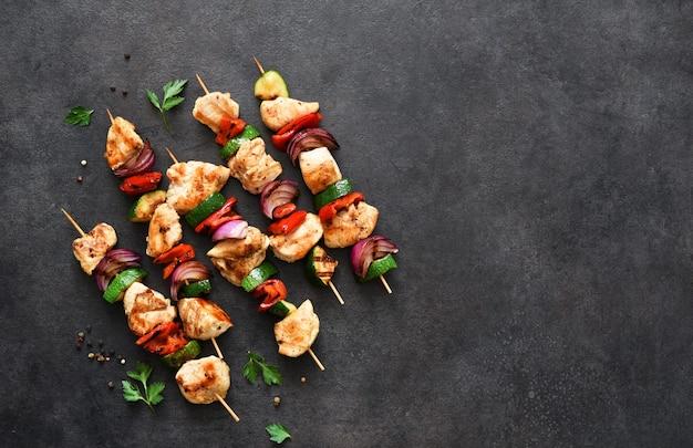 Куриный шашлык и овощи, перец, лук, кабачки на шпажках.
