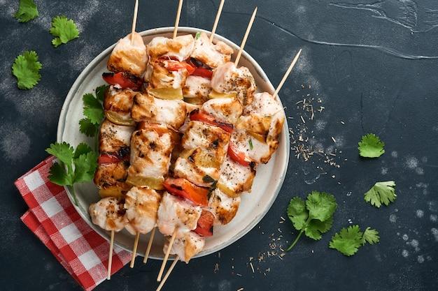 흰색 테이블 배경에 세라믹 접시, 향신료, 실란트로 허브 및 야채에 치킨 시시 케밥 또는 꼬치 케밥. 굴라시나 시시 케밥을 위한 바베큐 원시 재료. 평면도. 무료 복사 공간