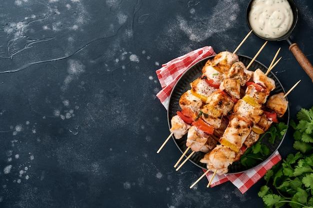 Куриный шашлык или шашлык на деревянной доске, специи, зелень, овощи