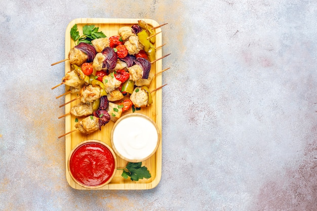Chicken shish kebab with vegetables,ketchup,mayonnaise,top view
