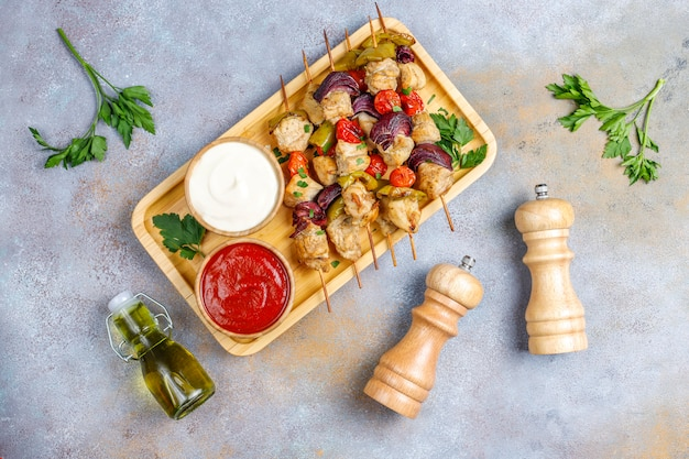 Chicken shish kebab with vegetables, ketchup, mayonnaise, top view