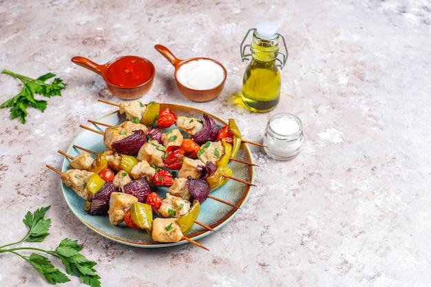 Chicken shish kebab with vegetables,ketchup,mayonnaise,top view