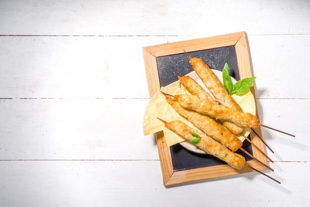 木製の串に刺したチキンシシカバブの上面図。ひき肉、日当たりの良い白い木製の背景のコピースペースと伝統的な地中海料理のケバブ