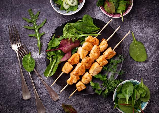 Chicken shish kebabs with green salad. selective focus