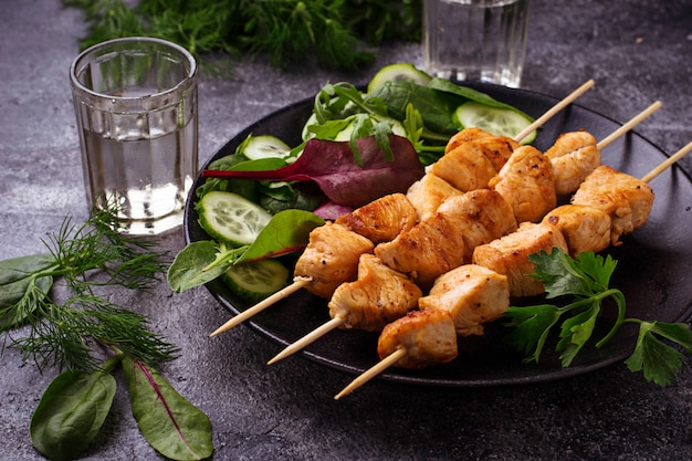 Chicken shish kebabs with green salad. selective focus