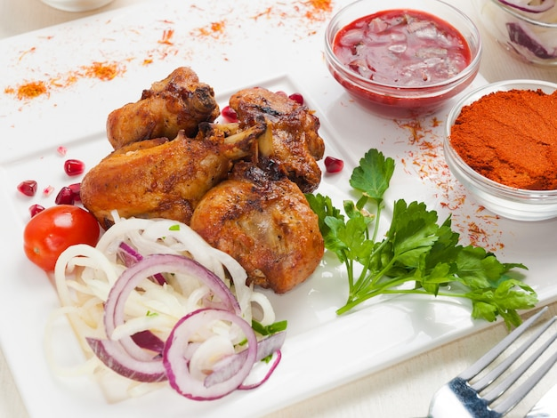 Chicken shish kebabs with green. with marinated onion and hot sauce