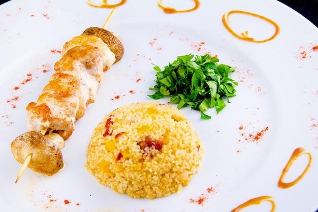 치킨 꼬치: 치킨 필레, 피망, 버섯, 야채를 곁들인 매운 쿠스쿠스, 파슬리를 곁들인 말린 토마토.