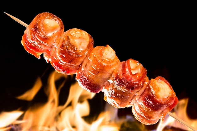 Chicken skewer with bacon over fire flames