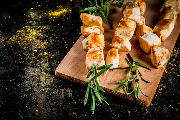 Chicken skewers with rosemary on a black rusty metallic background