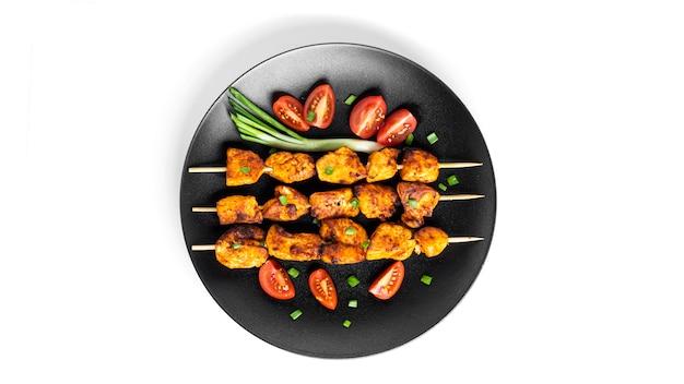 白で隔離の黒いプレートに野菜と鶏の串焼き。スブラキが分離されました。