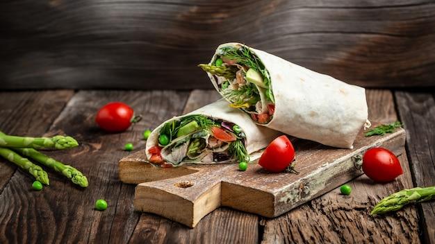 アスパラガス、アボカド、トマト、エンドウ豆、チーズ、タルタルソースを添えたトルティーヤラップのチキンスライス