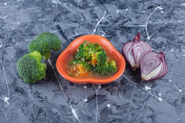 파란색 표면에 치킨 수프, 브로콜리, 양파