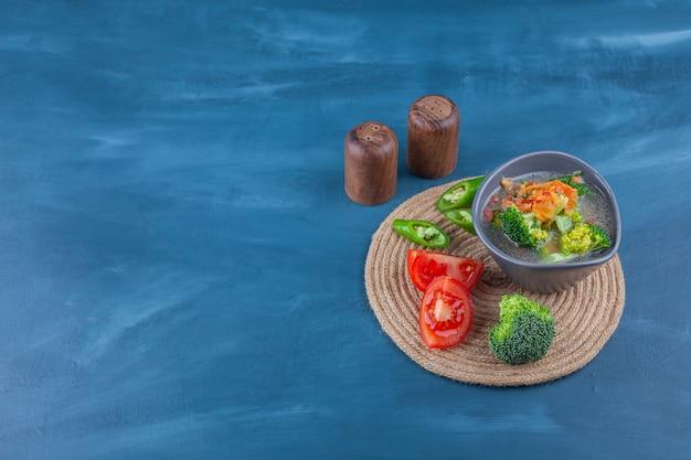 Куриный суп в миске и нарезанные овощи на подставке, на синем столе.