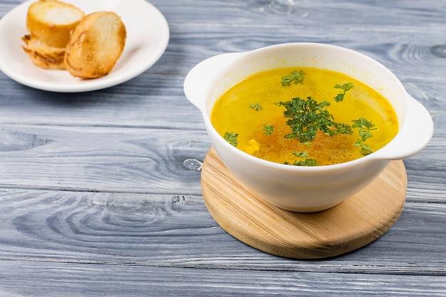 Куриный суп в белой тарелке с хлебом, на деревянном фоне