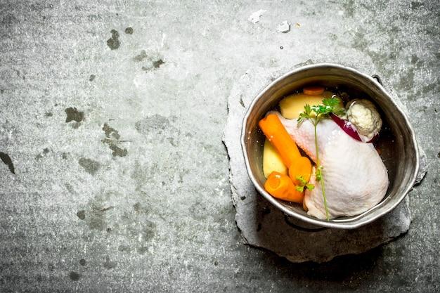 古い鍋に野菜を入れたチキンスープ。