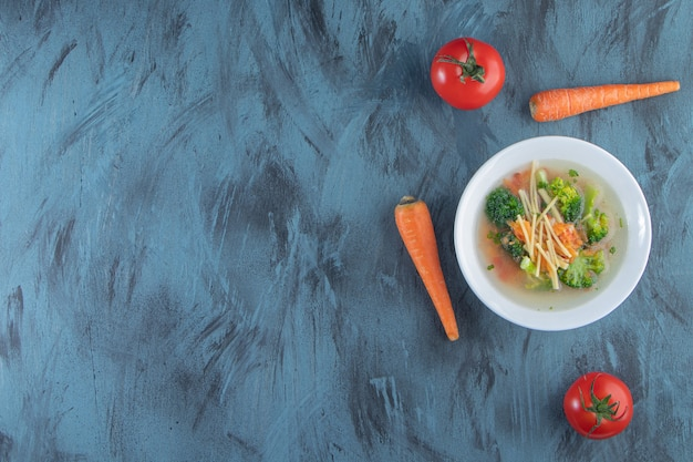Куриный суп с брокколи и морковью в миске рядом с овощами, на синем фоне.