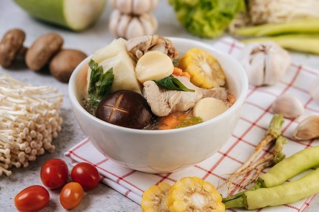Chicken soup with corn, shiitake mushroom, enoki mushroom, and carrot.