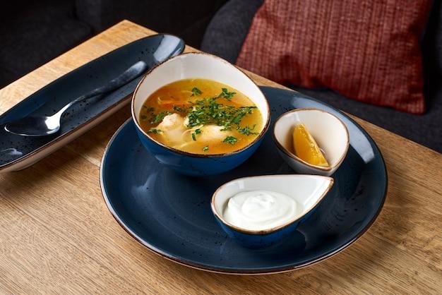 木製のテーブルに卵麺とチキンスープ。