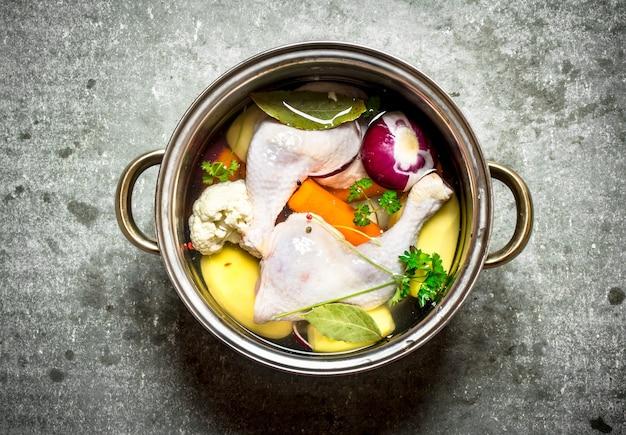 Куриный суп со свежими овощами. на каменном столе.
