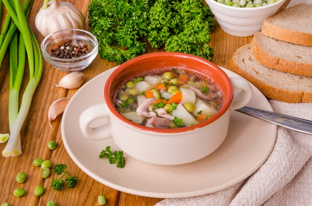 Chicken soup with green peas and vegetables in a bowl on a wooden background