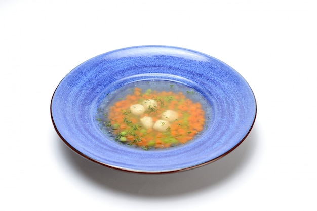 Chicken soup with meatballs and carrots in a blue plate