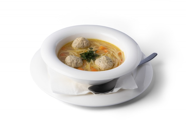 Chicken soup with meatballs on a white plate, for delivery
