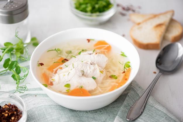 Куриный суп с лапшой и зеленью в белой тарелке