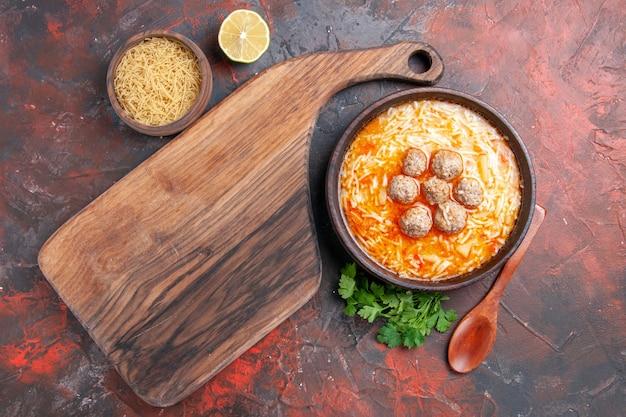 어두운 배경에 국수와 익히지 않은 파스타 레몬 채소와 커팅 보드가 있는 치킨 수프 스톡 이미지