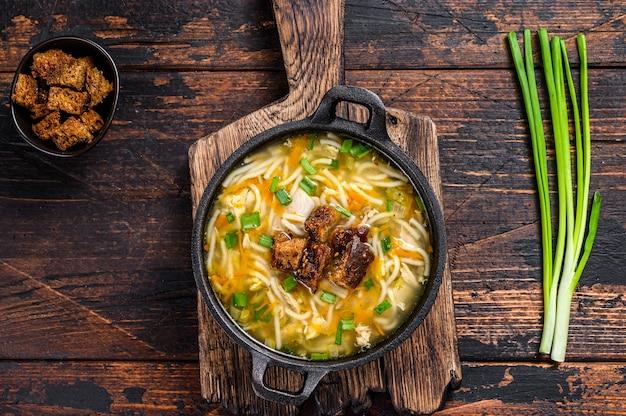 麺と野菜のチキンスープ。暗い木の背景。上面図。