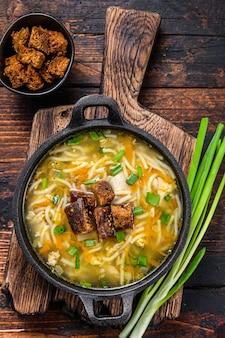 麺と野菜のチキンスープ。暗い木製の背景。上面図。
