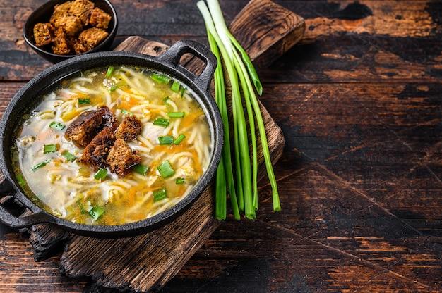 Куриный суп с лапшой и овощами. темный деревянный стол. вид сверху.