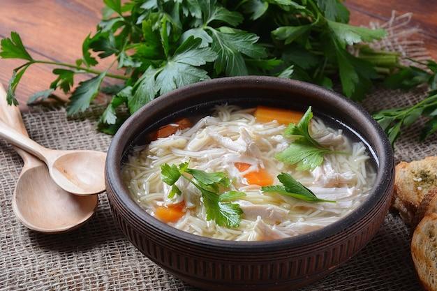 그릇에 국수와 야채와 치킨 수프.