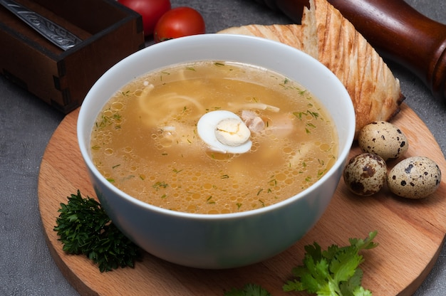 Chicken soup with noodles and quail egg on a wooden board
