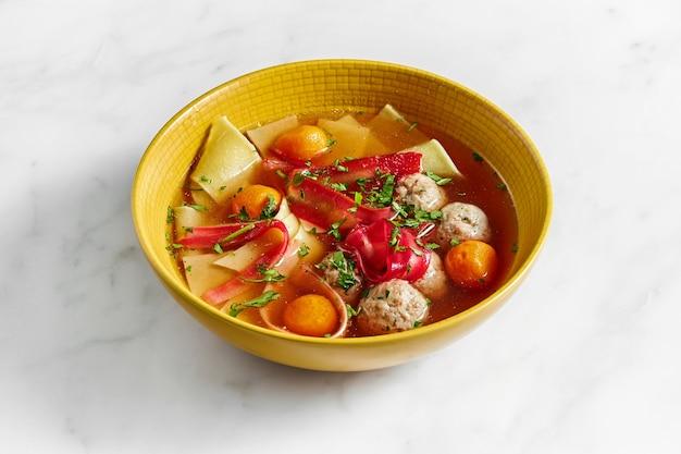 대리석 위에 노란색 그릇에 국수, 노른자, 미트볼, 허브가 들어간 치킨 수프