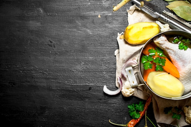 Chicken soup with potatoes, carrots and spices. on a black wooden background.