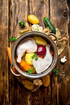 木製のテーブルの上の大きな鍋に野菜とチキンスープ。