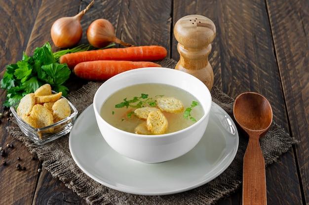 白いボウルに野菜とチキンスープ。木製の背景においしい自家製スープ。