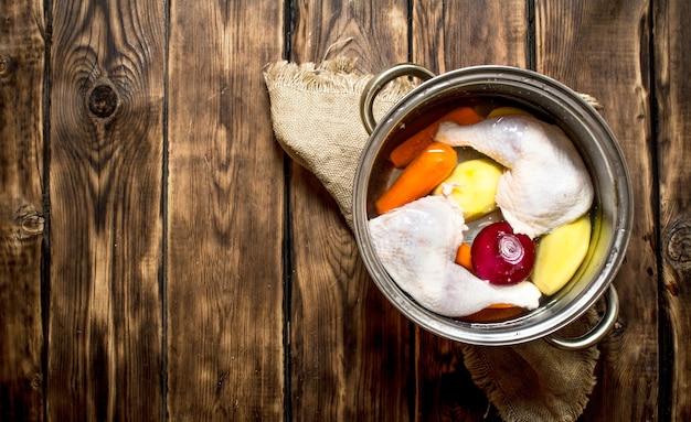 Куриный суп с овощами. на деревянном столе.