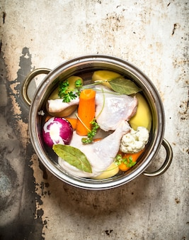 Chicken soup with vegetables. on rustic background .