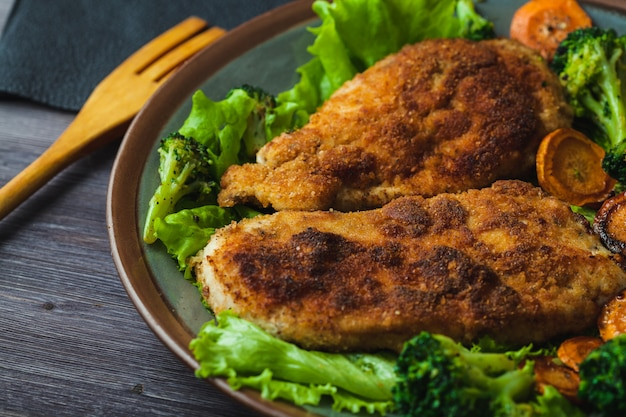 Chicken steak in breadcrumbs with vegetables on a plate