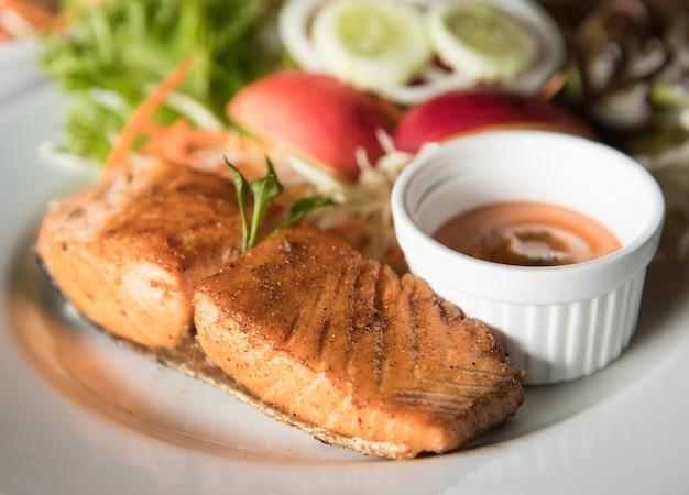Куриный стейк в белой тарелке с соусом для макания и овощами в фоновом режиме