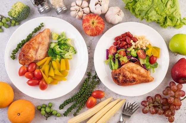 白い皿に白ごま、エンドウ豆、トマト、ブロッコリー、カボチャをトッピングしたチキンステーキ。