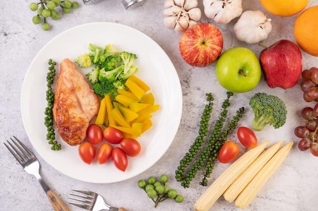 Bistecca di pollo condita con sesamo bianco, piselli, pomodori, broccoli e zucca in un piatto bianco.