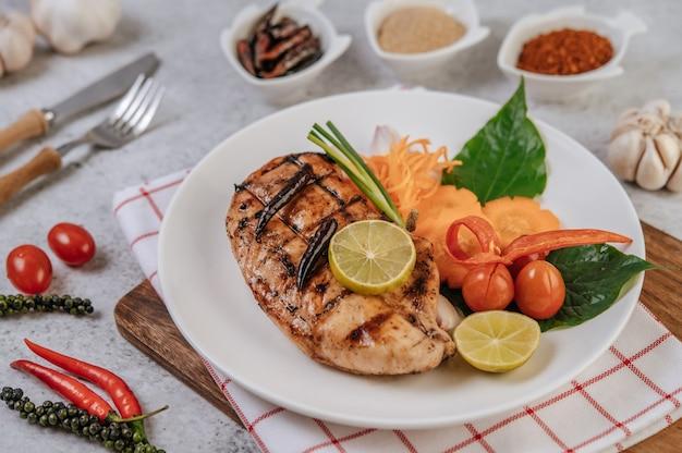 Куриный стейк с лимоном, помидорами, чили и морковью на белой тарелке.