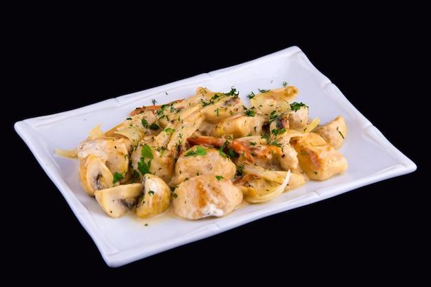 Chicken stew - chicken fillet, mushrooms, carrots, leeks, sour cream on white plate